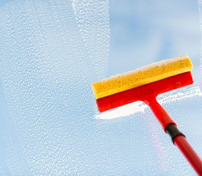 38676126 - people, housework and housekeeping concept -close up of hand cleaning window glass with sponge mop and foam
